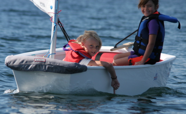 young children learning to sail on an optimist